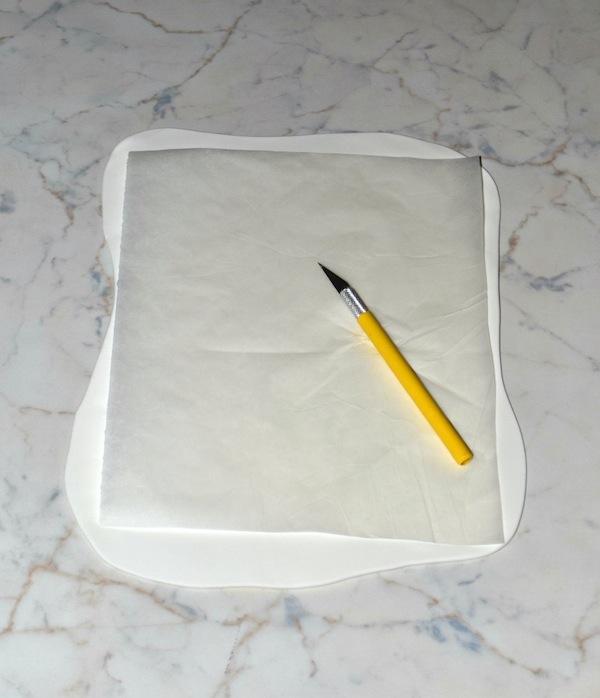 Stendete la pasta di zucchero bianca e riportate la grandezza della vostra base di pasta frolla su un foglio di carta forno.